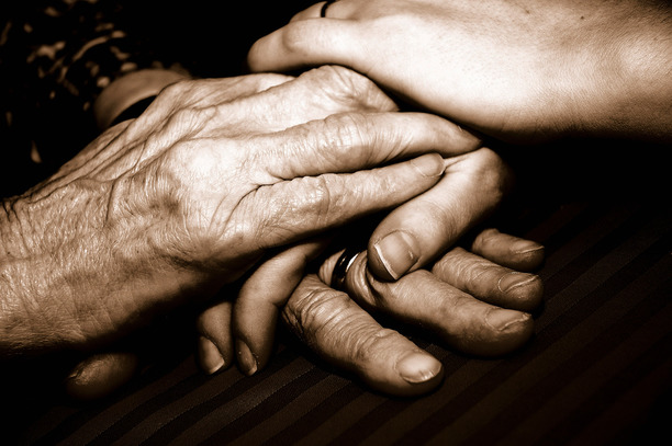 An older couple clasping hands.