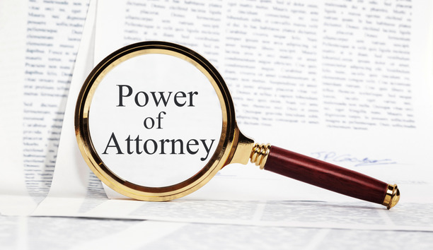 A magnifying glass showing 'Power of Attorney' over a pile of papers.