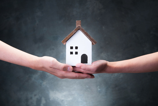 Two people, joining hands, holding a property model.