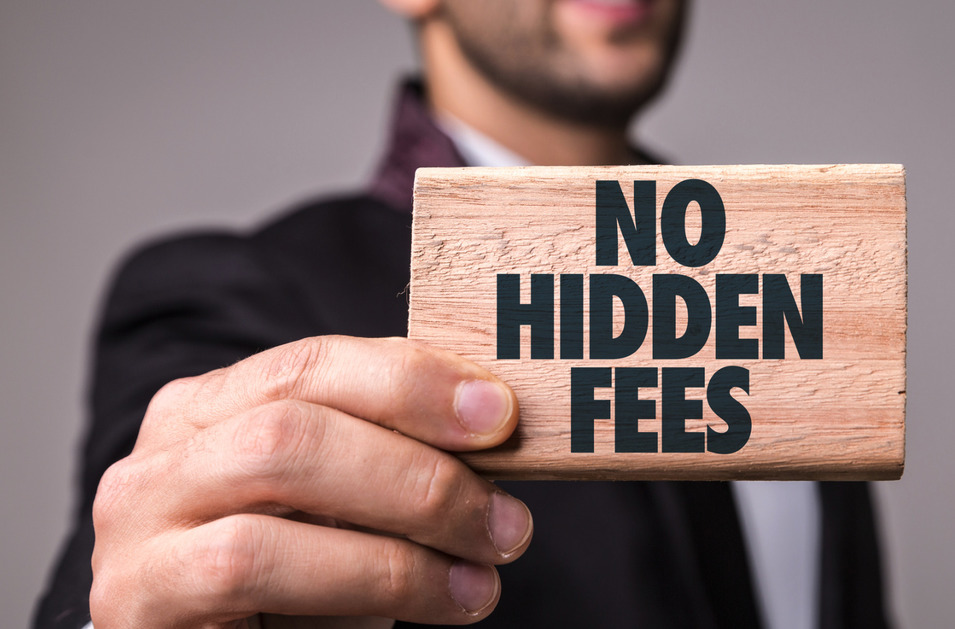 """No Hidden Fees"" on a wooden block, held by a man wearing a suite."