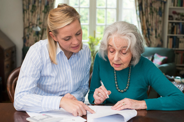 A lady helping an older lady to read through some documents.