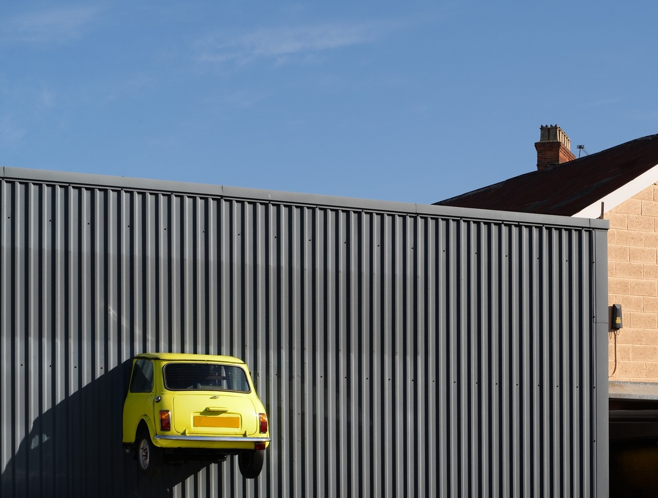 A yellow mini car stuck half-way through a building, having been involved in a Road Traffic collision