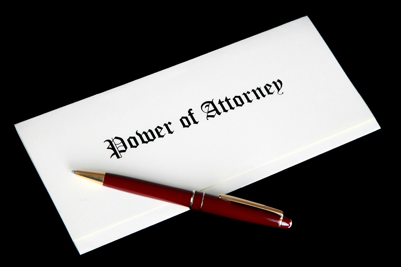 A piece of paper folded into three, with Power of Attorney written on, with a red pen resting on the document.