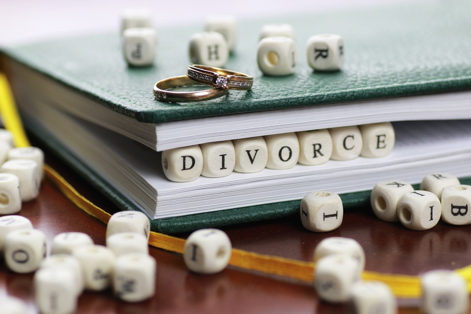 The word divorce written in cube letters in between the pages of a book, with a wedding band and a wedding ring resting on top of each other on the book, and other random letter cubes surrounding.