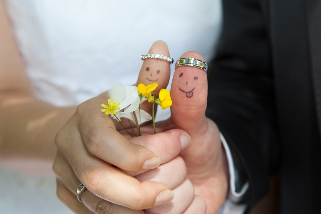 A couple wearing wedding attire, joining hands, with smiley faces drawn onto their thumbs, wearing their weddings rings
