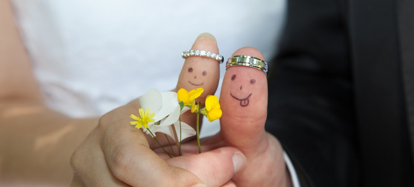 A Bride & Groom's thumbs with drawn smiley faces, holding four small flowers, wearing their wedding rings as crowns.