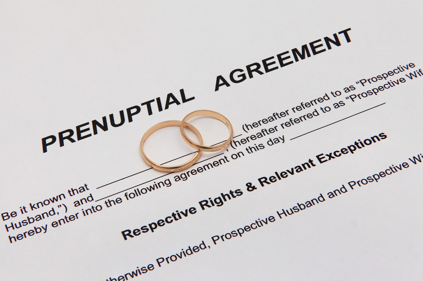 A prenuptial agreement, with two gold wedding rings on top.