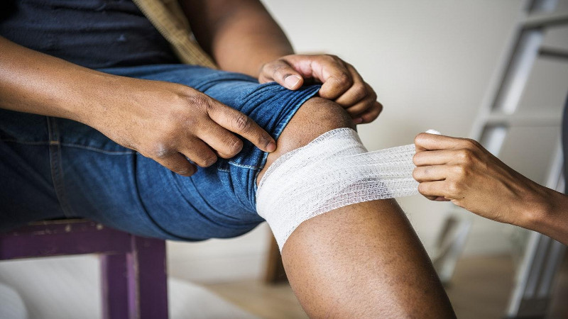 A person with a bandage being wrapped around their leg.