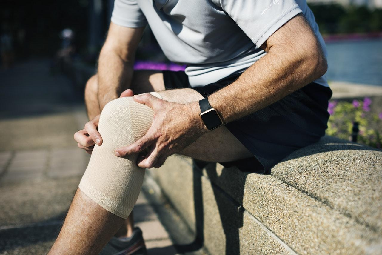 An injured man with his hands around his injured knee, with a  knee support sitting down on a wall
