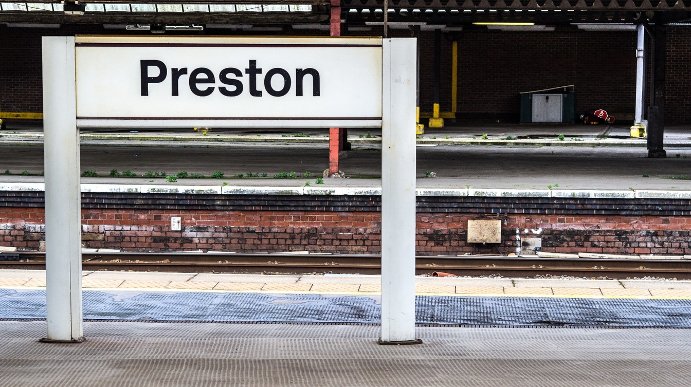 A sign showing Preston train station