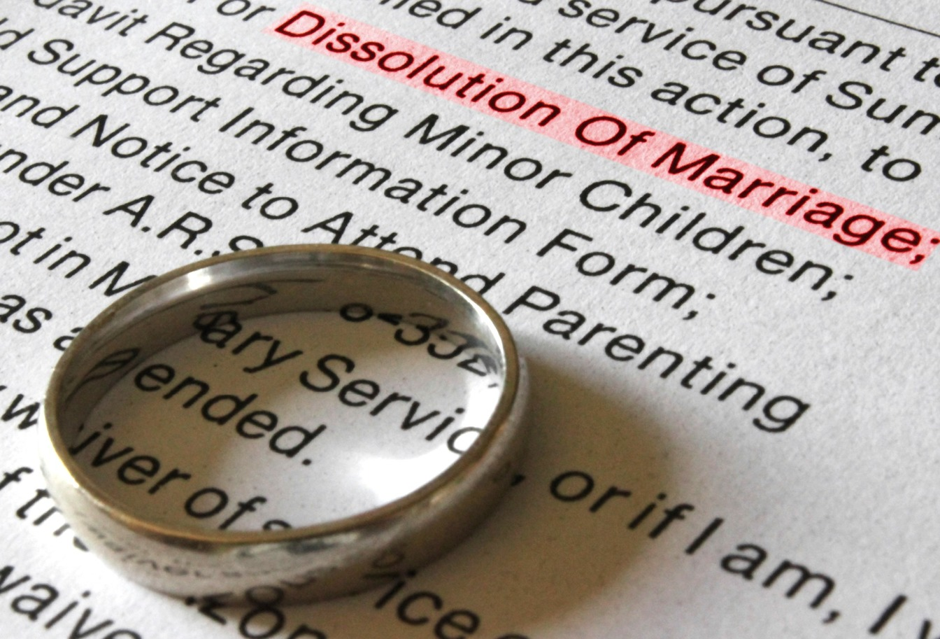 Gold wedding ring placed on divorce paperwork with Dissolution of Marriage highlighted