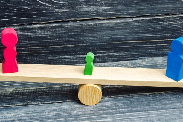 A wooden see-saw, with a pink figure on one end,a blue figure on the other, and a small green figure in the middle.