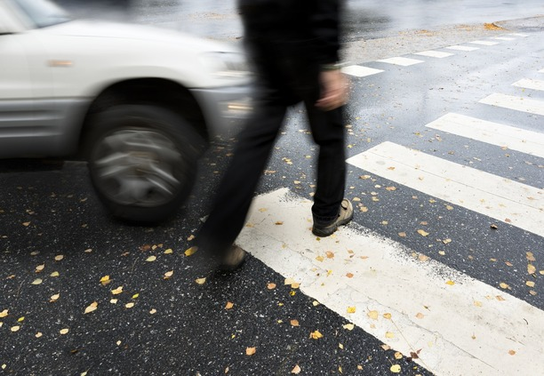 A person crossing a zebra crossing, being hit by a car.
