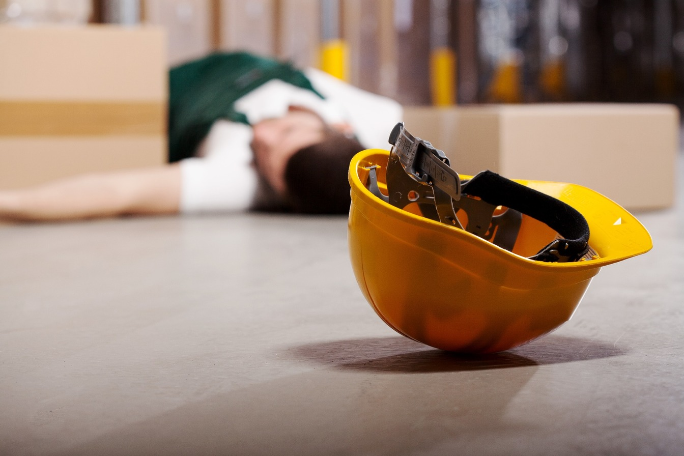 A man who has suffered from a fall at work, lying on the floor, with his hard hat just out of his reach.