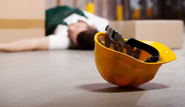 A man who has been injured at work, laying on the floor.  His hard hat has rolled away from him.