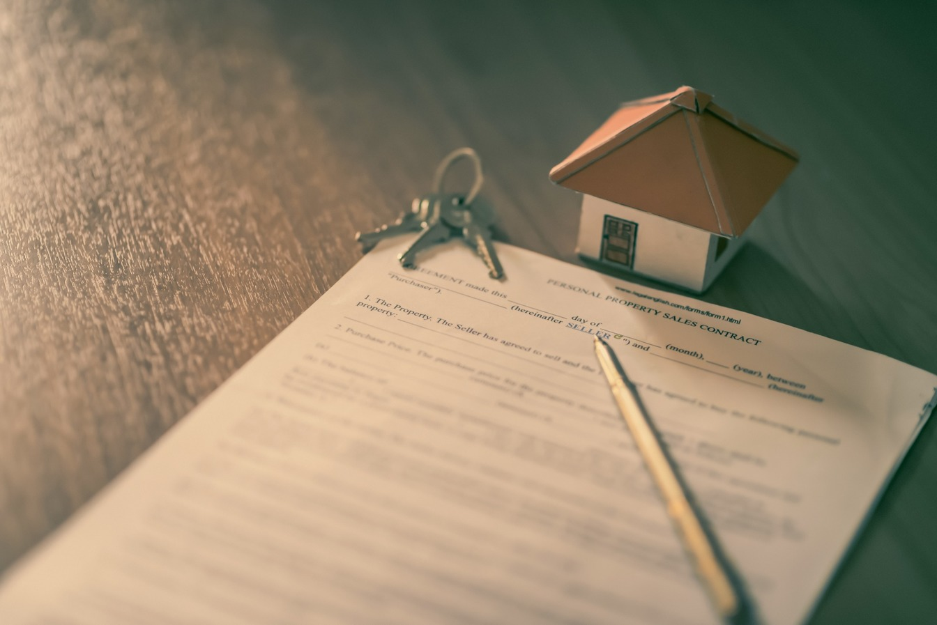 A Property Sales Contract template, with a miniature cardboard house and a set of keys.