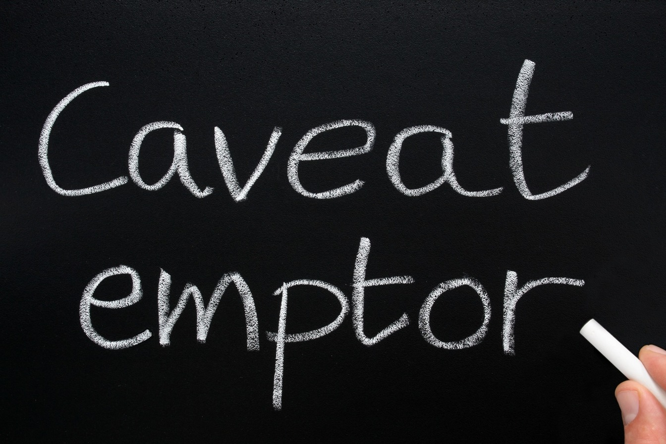 'Caveat Emptor' written on a black board in white chalk