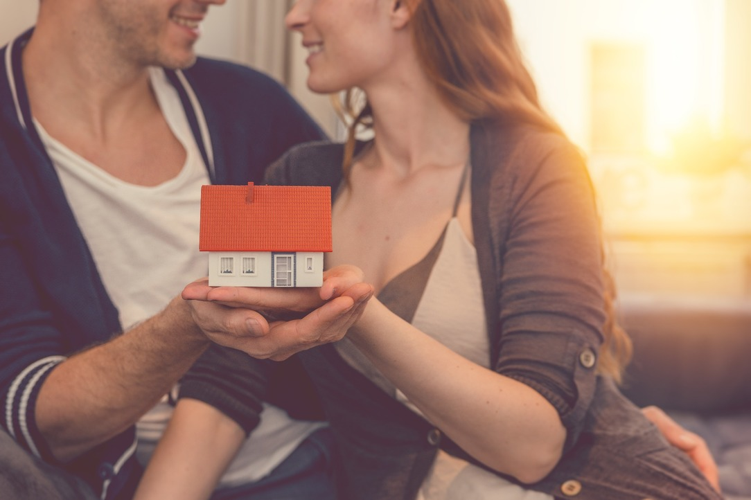 A couple holding a property model in their hands.