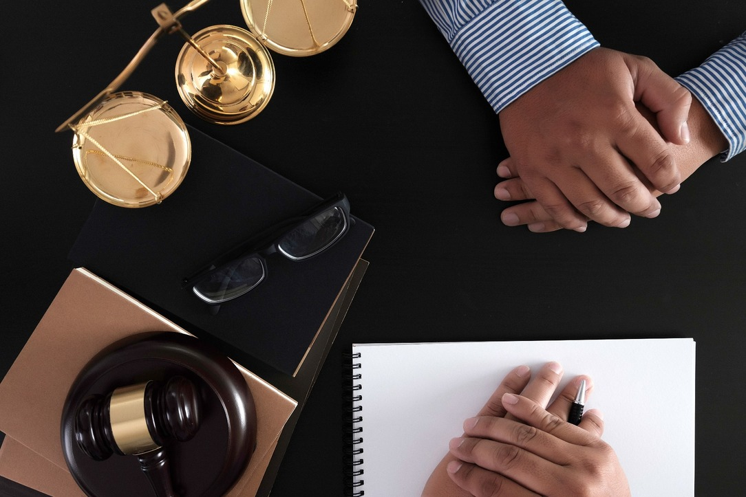 Two people sat at a table, with notepads and legal tools surrounding them.