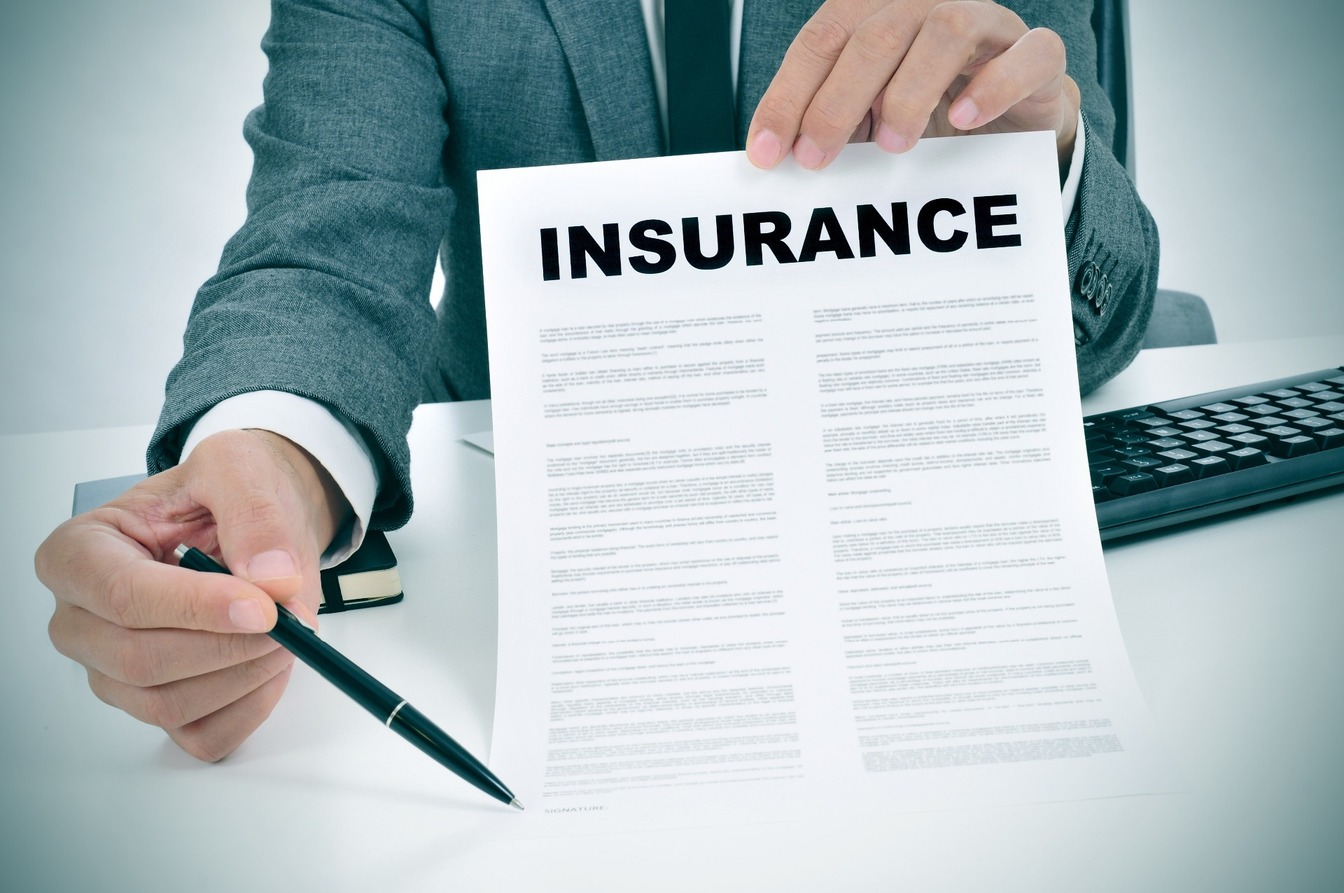 A smartly dressed man holding out a form with 'INSURANCE' written across the top, pointing to the signature section with a pen.