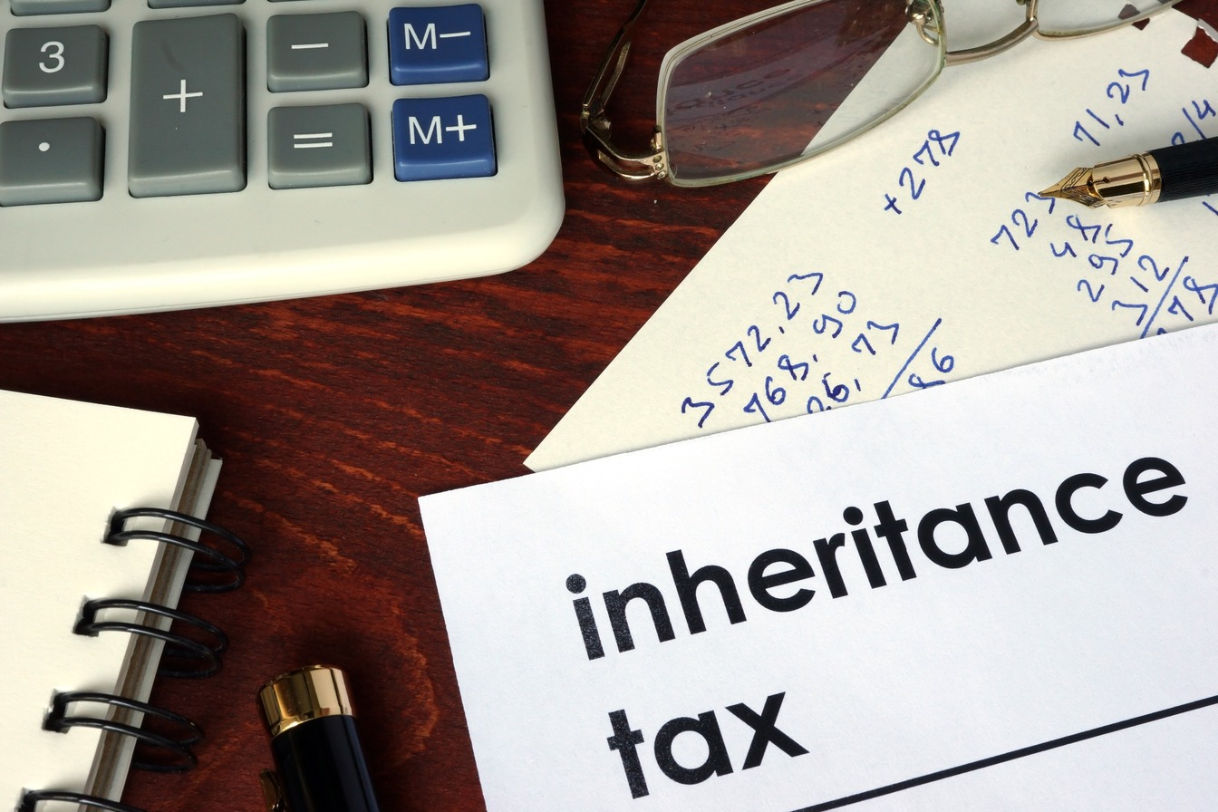 Inheritance Tax calculation with a calculator, fountain pen and notepad