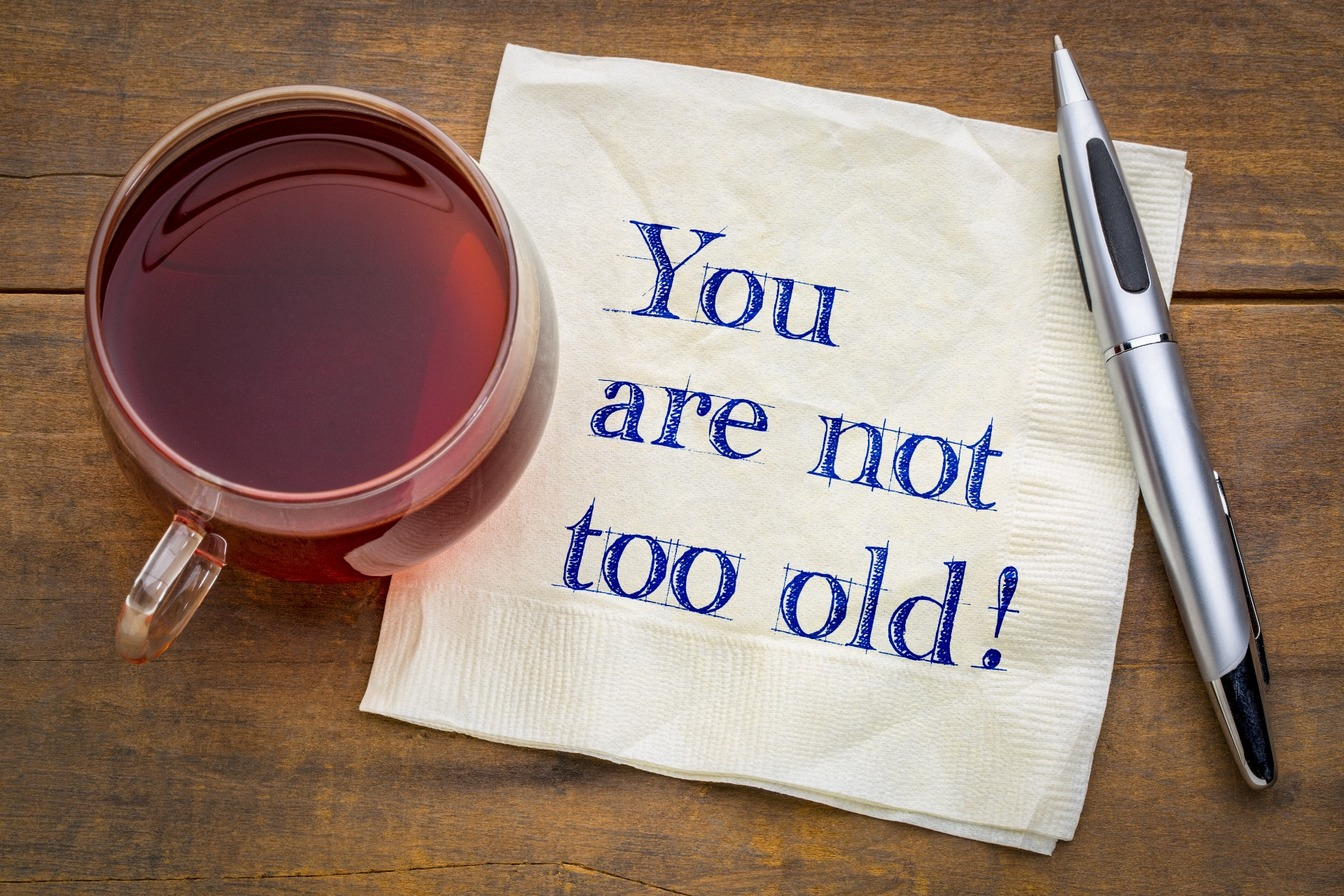 You are not too old, written on a napkin with a cup of tea and a silver pen resting on the napkin