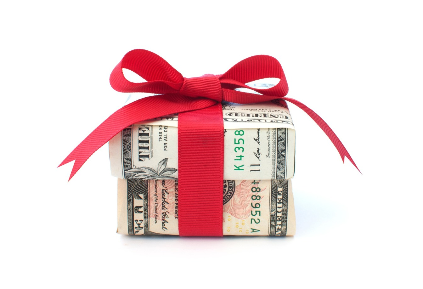 A present made of money and wrapped in red ribbon