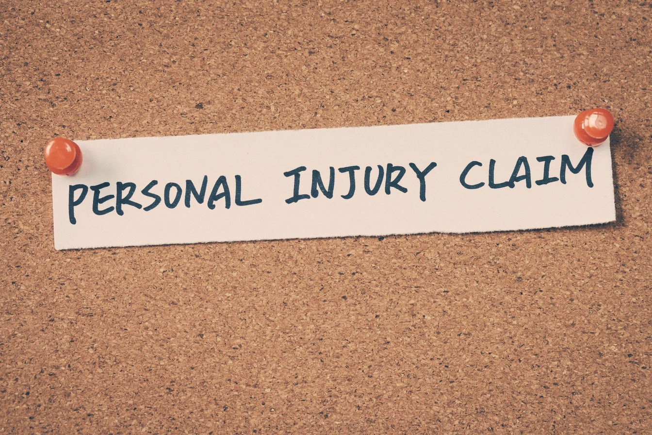 Personal Injury Claim written on a piece of paper and pinned to a cork board.
