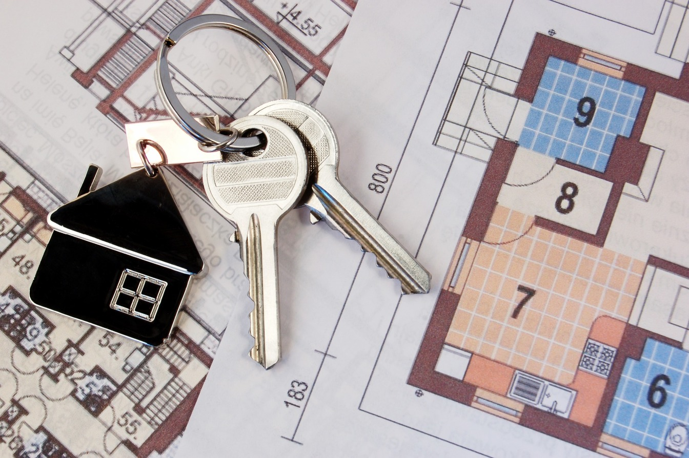 A pair of silver keys, with a black house keyring, laid on plans for a property