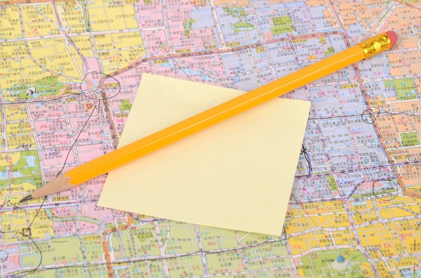 A map, with sticky notes, and a pencil resting on top.