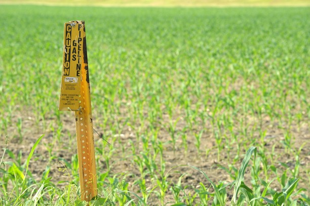 Caution 'Natural Gas' sign in a field.
