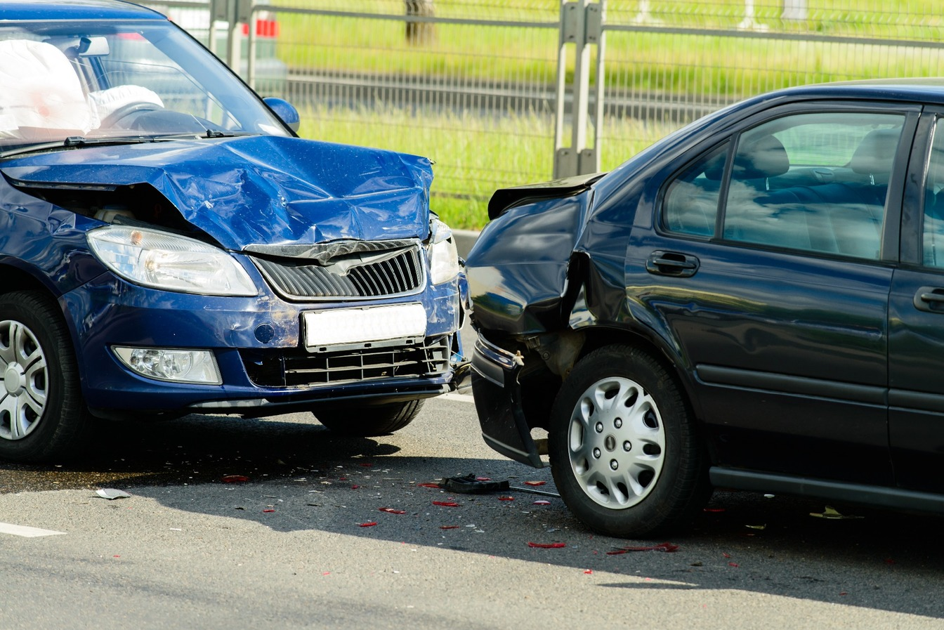 A blue car with a smashed bonnet, rear-ending a black car.