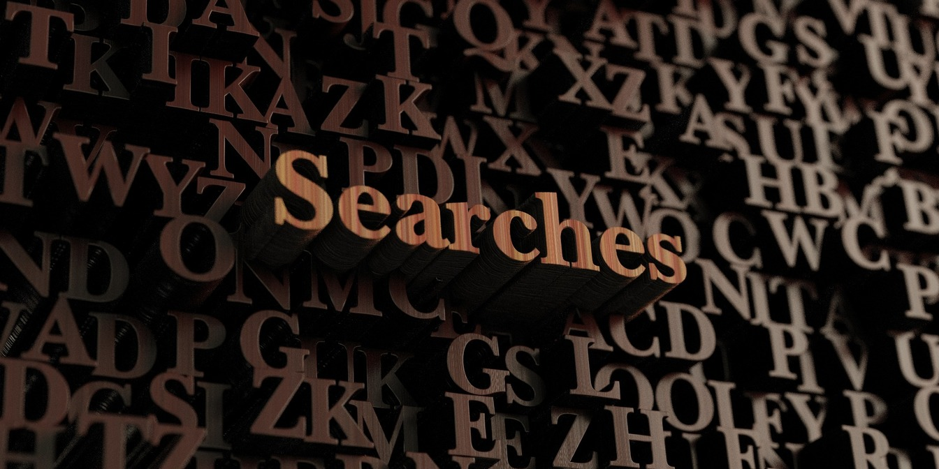 'Searches' spelled in wooden lettering, surrounding by a mix of other wooden letters.