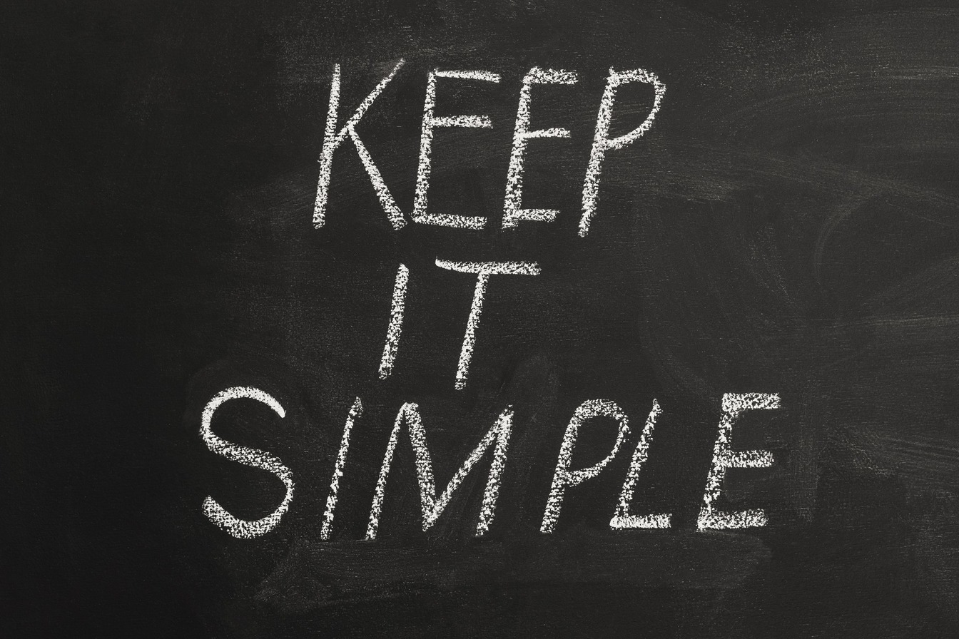 'Keep it Simple' written in white chalk on a black board