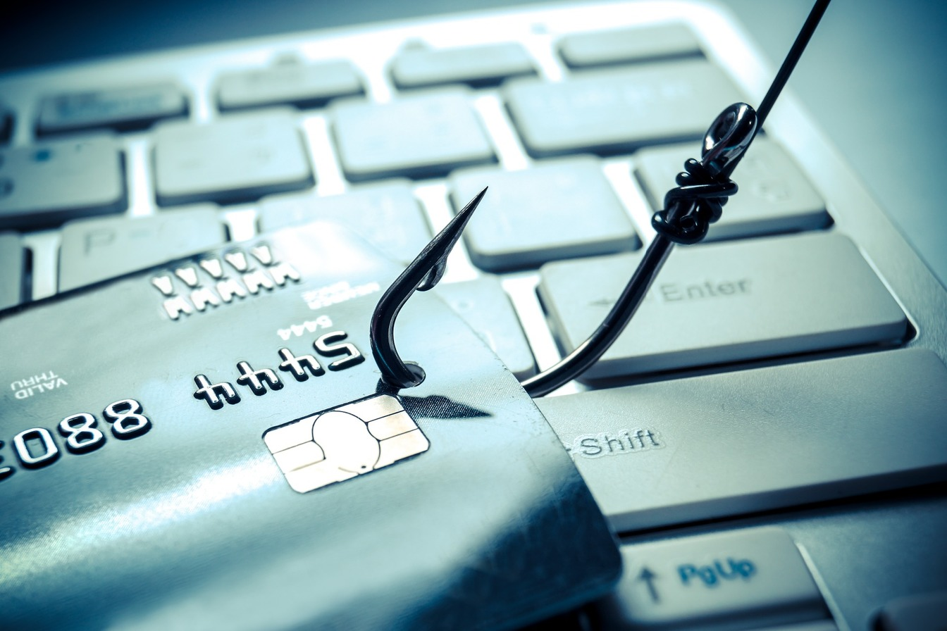 A fishing hook attached to a credit or debit card, pulling the information away from the computer keyboard.