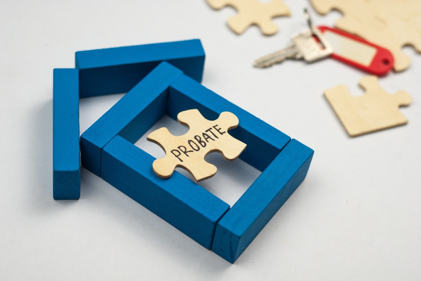 A wooden puzzle piece with 'Probate' written on in black pen, resting on a blue, block wooden house.