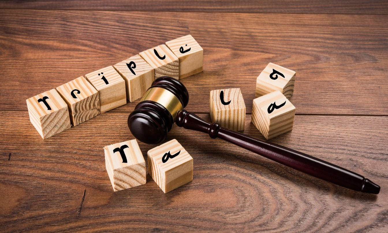 Wooden cubes spelling out 'Triple' consecutively and then the broken word 'Talaq' surrounding a gavel