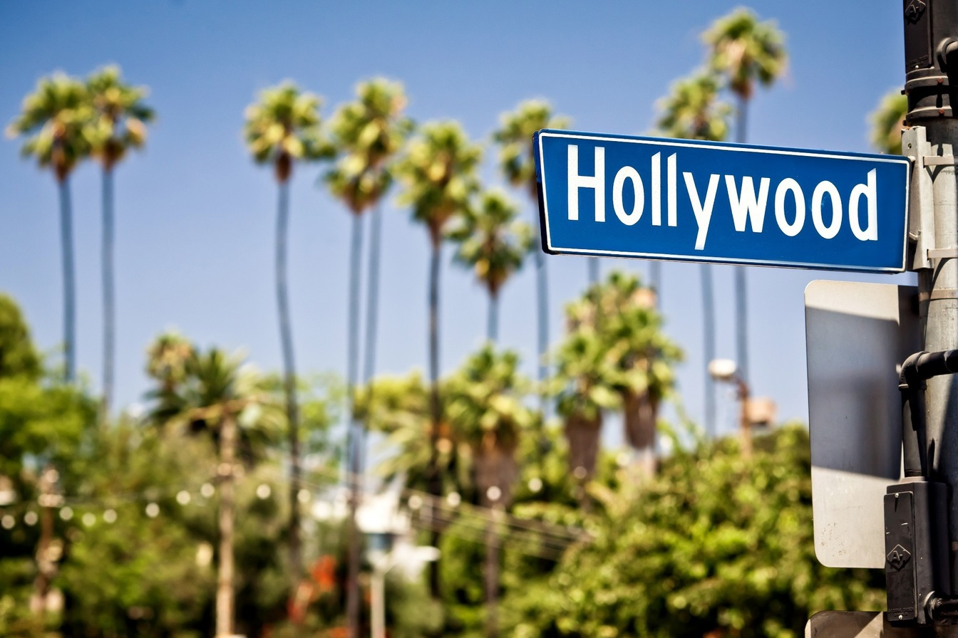 A blue sign post for 'Hollywood' in white lettering, with large trees behind.