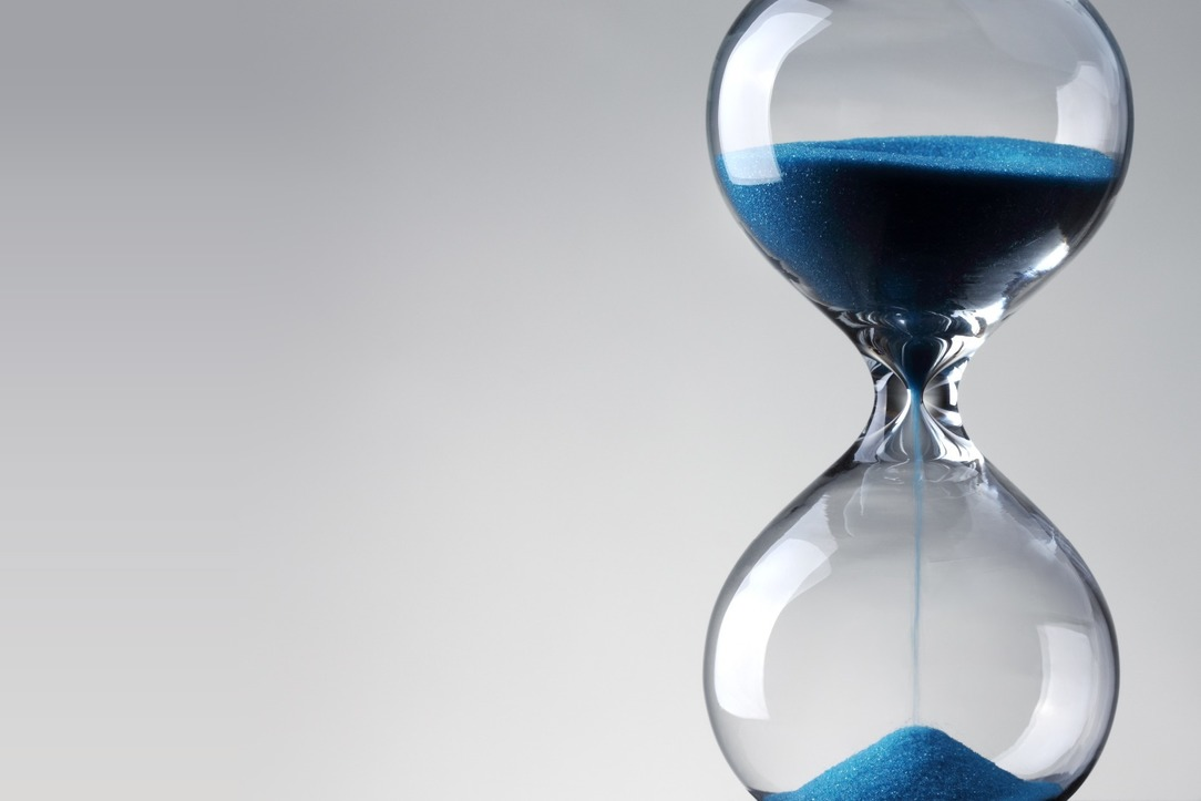 An hourglass with blue sand.