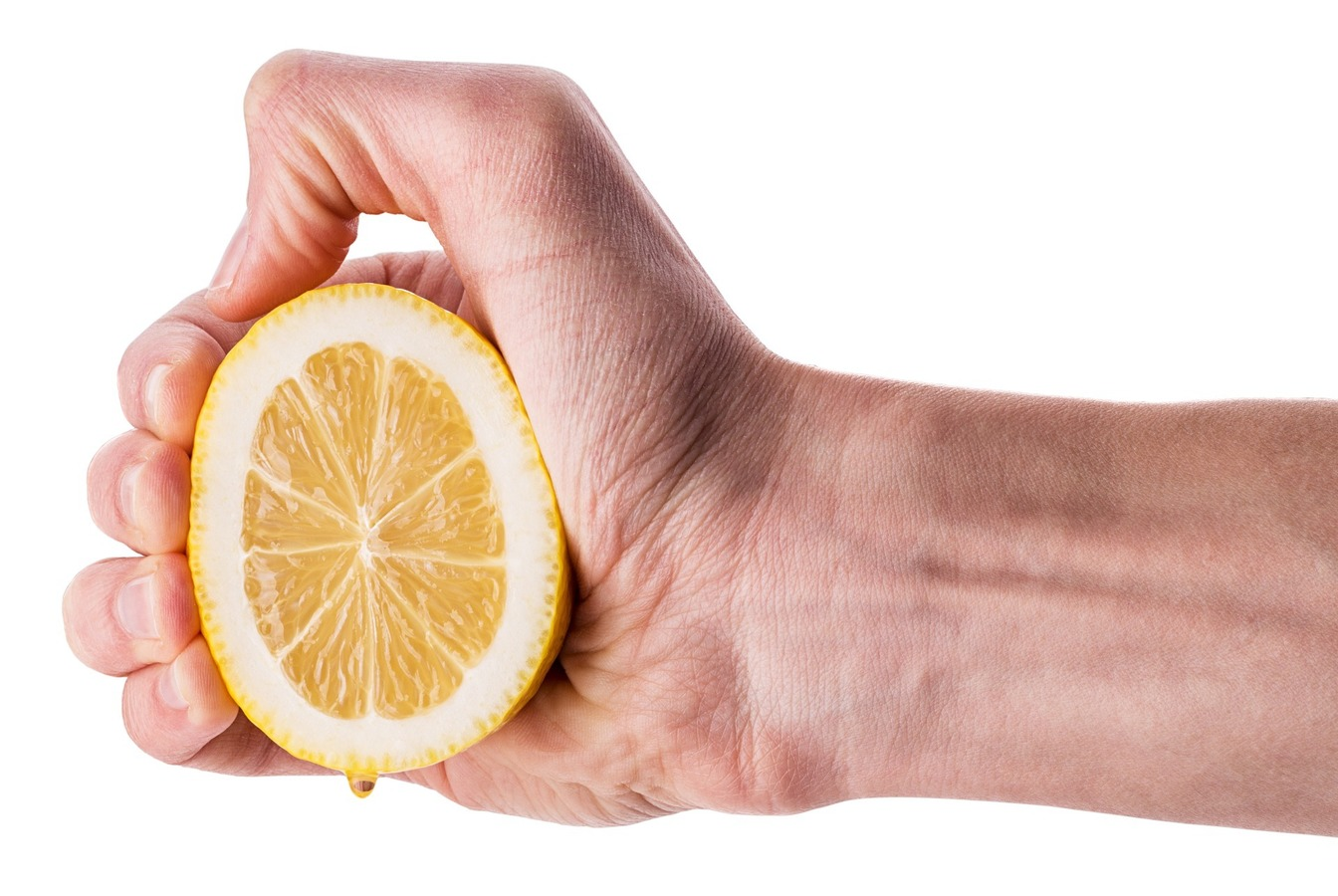 A hand squeezing half a lemon, with some juice dripping down
