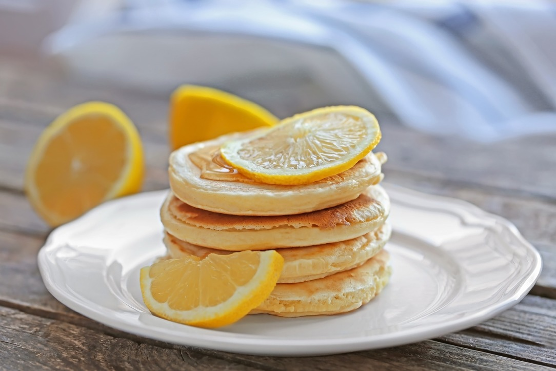 A stack of small, evenly sized pancakes with lemon slices on top.