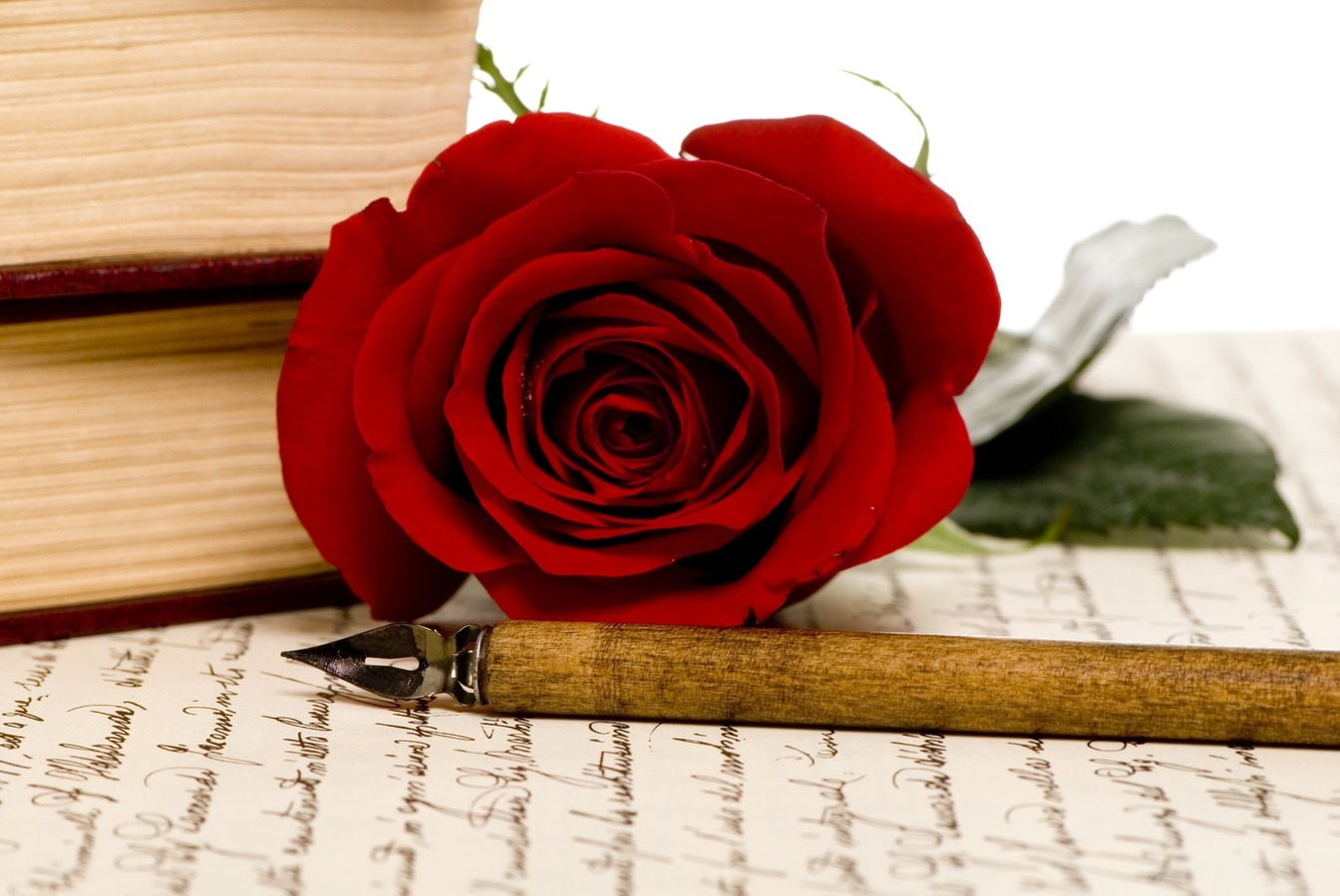 A red rose, resting next to two books, on top of a Will with a pen