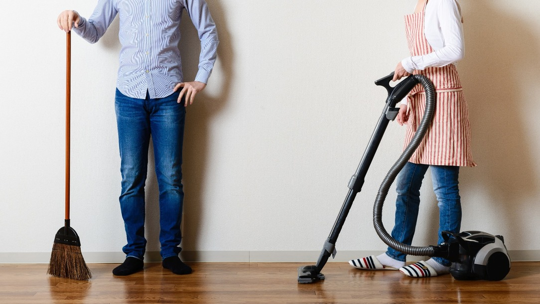 A couple, one holding a broom, and the other stood away, holding a hoover.