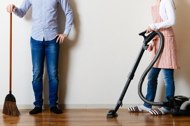 A couple with different household cleaning items, such as a broom and hoover.