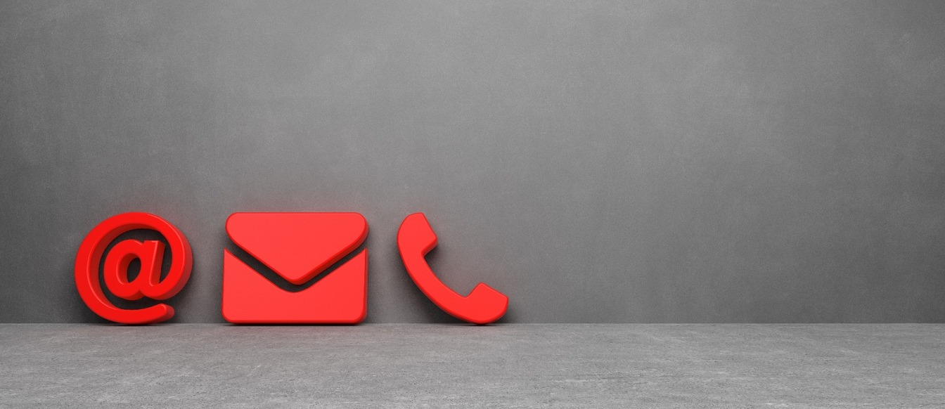 A red '@' sign, an e-mail envelope and a telephone cut-outs against a black background