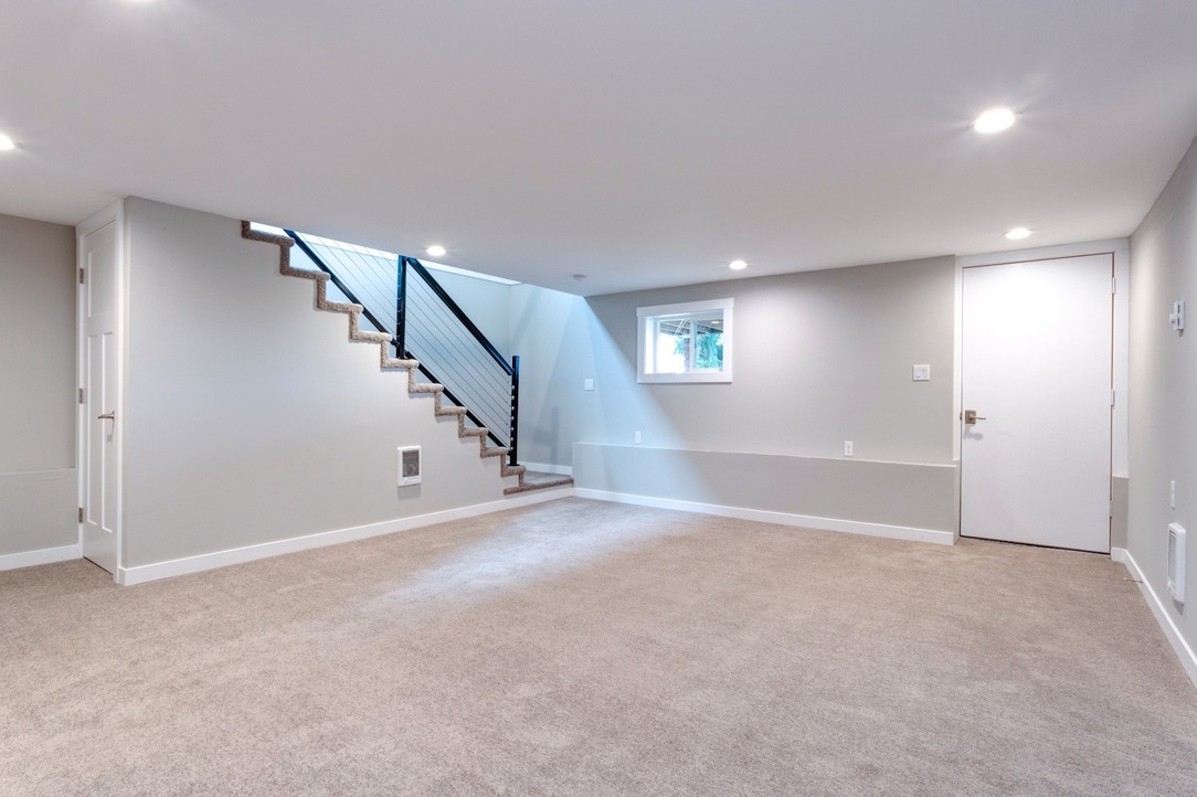 A well-lit basement which has been freshly renovated, with light grey walls and bright white ceilings and doors, with spotlights