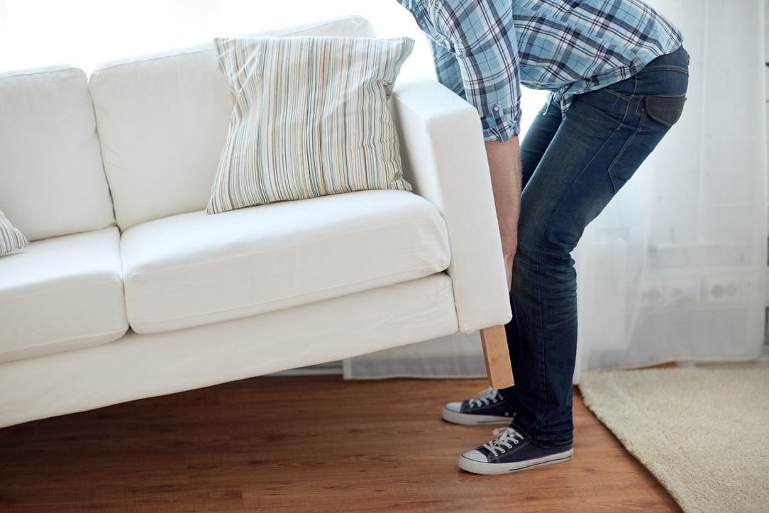 A man lifting a sofa, as he moves it around.
