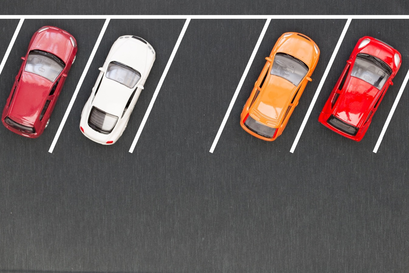 A row of car parking spaces, with a red and white car parked, with an empty space inbetween, and an orange and red car parked in the final two spaces.