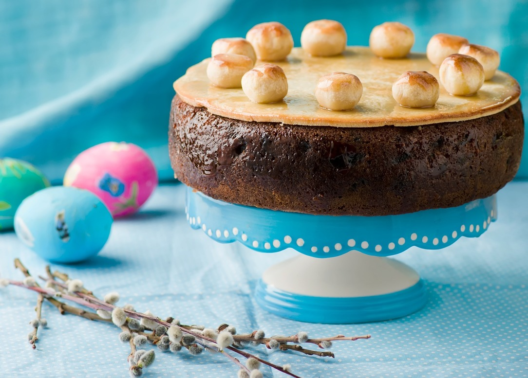 A traditional Simnel cake, on a blue and white cake stand, with a green, blue and pink faux egg and some flowers around the bottom of the stand.