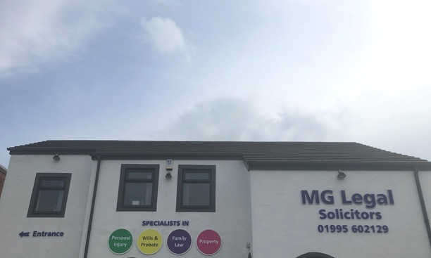 MG Legal's Garstang office with the four different coloured ball signs, an entrance sign and MG Legal Solicitors 01995602129